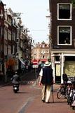 Oude mens met een riet die in Jordaan, Amsterdam lopen Stock Afbeelding