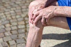 Oude mens met knoestige handen die zijn knie clutching royalty-vrije stock fotografie