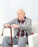 Oude mens met riet thuis Royalty-vrije Stock Foto's