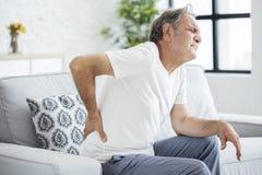Oude mens met rugpijn stock afbeeldingen