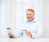 Oude mens met tabletpc en creditcard thuis Royalty-vrije Stock Foto's