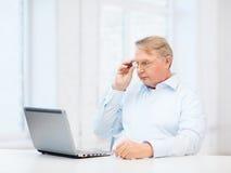 Oude mens in oogglazen die met laptop thuis werken stock foto