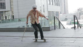 Oude mens op een skateboard stock footage