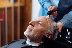 Oude mens tijdens het wassen van zijn haar in kapperswinkel royalty-vrije stock afbeeldingen