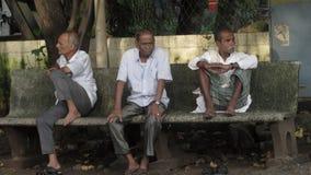 Oude mensen die bij de bank die van het strand zitten op de bus wachten stock foto