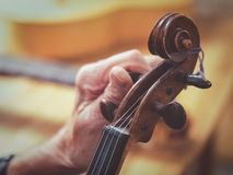 Oude mensen meer luthier handen die verouderde viool stemmen Stock Afbeelding