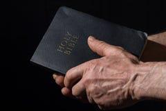 Oude mensen` s handen die de Bijbel houden Royalty-vrije Stock Foto