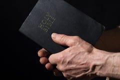 Oude mensen` s handen die de Bijbel houden Royalty-vrije Stock Afbeelding