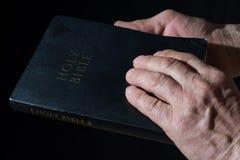 Oude mensen` s handen die de Bijbel houden Rustig licht Royalty-vrije Stock Fotografie