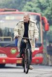 Oude mensencycli in de vroege ochtend met bus op achtergrond, Guangzhou, China Stock Foto