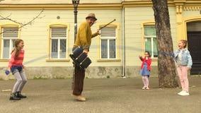 Oude mensenkabel die met drie meisjes overslaan stock video