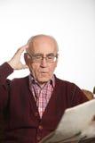 Oude mensenlezing newspapper stock afbeeldingen