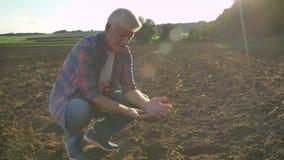 Oude mensenzitting en het onderzoeken van grond van gebied met zijn één hand, opstaand en rond kijkend, moderne landbouwer stock footage