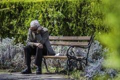 Oude mensenzitting op een bank in het overzeese park van Burgas/Bulgarije/04 18 2015/ stock afbeeldingen