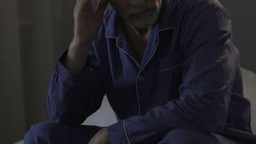 Oude mensenzitting op rand van bed in donkere ruimte die problemen met slaap, slapeloosheid hebben stock videobeelden