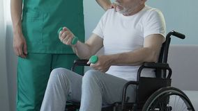 Oude mensenzitting in rolstoel, holdingsdomoren, die aan verpleegster, terugwinning spreken stock video