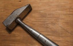 Oude metaalhamer op een houten oppervlakte stock afbeeldingen