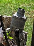 Oude metaalmelkemmer in de zon als tuindecoratie Stock Foto