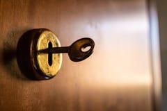 Oude metaalsleutel binnen het slot met de houten deur vage achtergrond stock fotografie