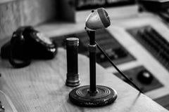 Oude microfoon met telefoon op achtergrond stock foto
