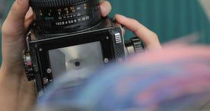 Oude middelgrote formaatcamera in de handen van een hipstermeisje, close-up, filmcamera stock videobeelden