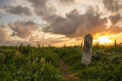 Oude mijlpaal bij zonsondergang. Ierland Royalty-vrije Stock Foto's