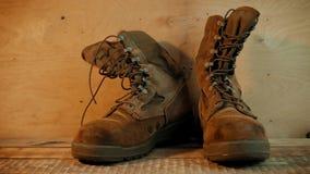 Oude militaire laarzen op een houten lijst stock video
