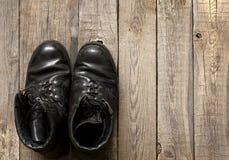 Oude militaire schoenen op houten raad Royalty-vrije Stock Foto