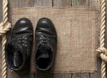 Oude militaire schoenen op houten raad Stock Afbeeldingen