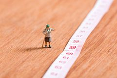 Oude miniatuurreiziger met 60ste aantal leeftijd bij het meten van band royalty-vrije stock afbeelding