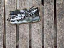Oude mobiele handige van de telefoontouchscreen en lezing glazen Stock Foto's