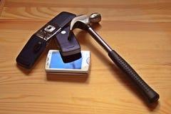 Oude mobiele telefoons met hamer stock foto