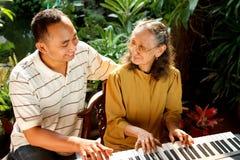 Oude moeder en zoons het spelen piano stock afbeeldingen