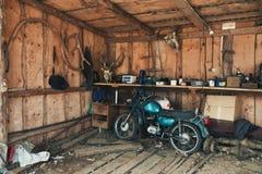 Oude Motor in een Schilderachtige Schuur Uitstekende Motorfiets in Oude Hangaar met Vele Zeldzame Voorwerpen Stock Foto's
