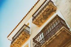 Oude muur met schilverf, gekrast uitstekend pleister en balkons met een roestig ijzer gesmeed rooster royalty-vrije stock fotografie