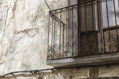 Oude muur met schilverf, gekrast uitstekend pleister en een balkon met een roestig ijzer gesmeed rooster stock afbeelding