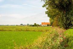 Oude Nederlandse boerderij met een oranje betegeld dak stock foto
