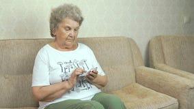 Oude oma die een mobiele telefoon thuis houden stock footage