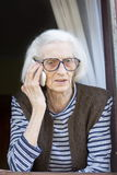 Oude oma die op de telefoon spreken die zich op haar venster bevinden Royalty-vrije Stock Afbeeldingen