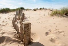 Oude omheining die een heuvel op zandig strand leiden royalty-vrije stock afbeeldingen