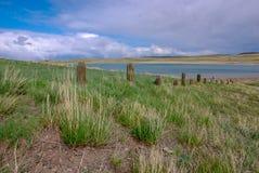 Oude omheiningslijn dichtbij meer in boerderijland Montana stock afbeeldingen