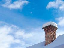 Oude, ongebruikte die schoorsteen met sneeuw wordt behandeld stock afbeelding