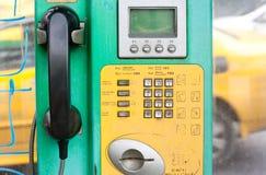 Oude openbare telefoon met munten Stock Afbeeldingen