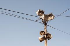 Oude openlucht openbare luidsprekers, megafoons en reflectors op metaalpool met zwarte elektrische kabels stock afbeeldingen