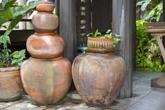 Oude oranje aarden die kruiken naast een houten pool worden gestapeld stock foto's