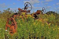 Oude oranje die tractor in onkruid wordt begraven Stock Afbeeldingen