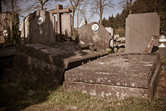 Oude overgehelde en beschadigde graven stock foto
