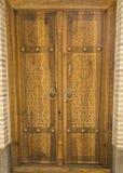 Oude overladen houten deur met mooie gravures stock afbeelding
