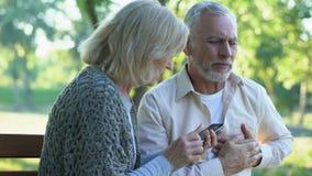 Oude paarzitting op bank, mens die aan aritmie, vrouw lijden die noodsituatie roepen stock footage