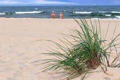 Oude paarzitting op een leeg strand Stock Foto